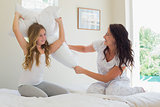 Mother with daughter pillow fighting in bed at home