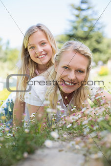 Girl lying on top of mother in park