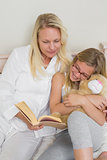 Mother and daughter reading story book in bed