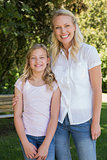 Mother with arm around daughter standing in park