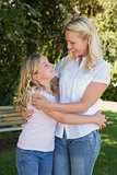 Happy mother and daughter embracing in park