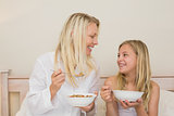 Mother and daughter having cereals in bedroom