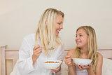 Mother and daughter having cereals in bedroom