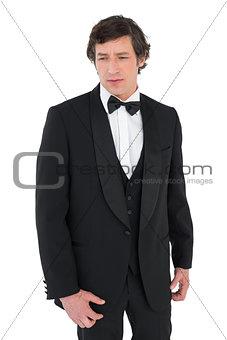 Anxious groom in tuxedo looking down