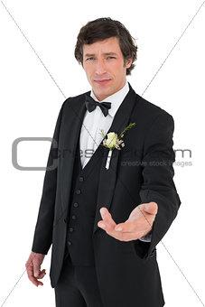 Confident groom in tuxedo offering hand
