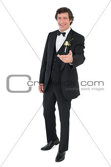 Happy groom in tuxedo offering hand