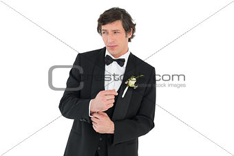 Groom in tuxedo adjusting cuff link