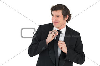 Happy groom adjusting necktie
