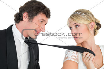 Bride pulling tie of groom