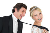 Attractive bride pulling tie of groom