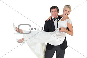 Happy groom carrying bride