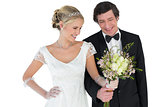 Loving newlywed couple holding bouquet
