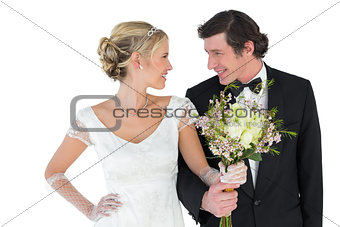 Newlywed couple with bouquet looking at each other