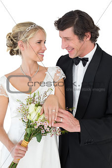 Bride and groom wearing wedding rings over white background