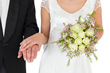 Mid section of bride and groom with rose bouquet