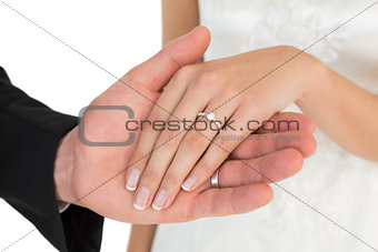 Cropped image of newly wed couple holding hands
