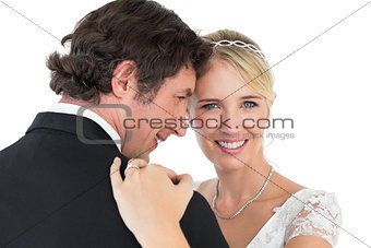Bride embracing groom over white background
