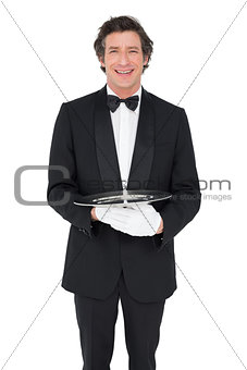 Happy waiter holding empty tray over white background