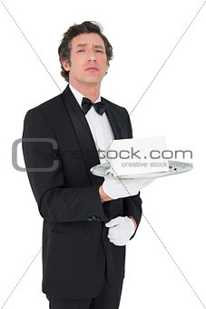 Confident waiter holding tray against white background