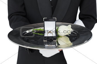 Mid section of waiter presenting engagement ring and rose