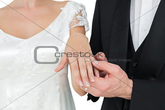 Bride and groom showing wedding ring against white background