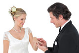 Attractive bride and groom exchanging wedding ring