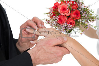 Groom and bride with flowers exchanging wedding ring