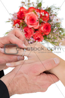 Cropped image of bride and groom exchanging ring