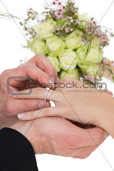 Cropped image of groom and bride exchanging ring
