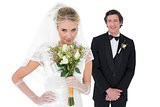 Bride smelling flowers while groom standing in background