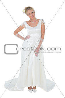 Beautiful bride with hand on waist over white background
