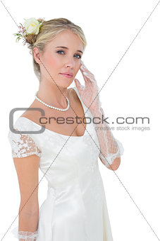 Confident bride touching cheek over white background