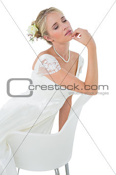 Bride with eyes closed leaning on chair