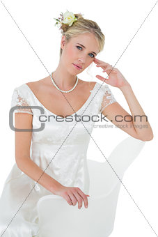 Beautiful bride sitting on chair over white background
