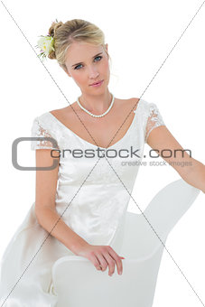Attractive bride sitting on chair over white background