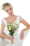 Bride holding flower bouquet while sitting on chair