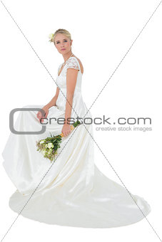 Portrait of bride holding bouquet over white background