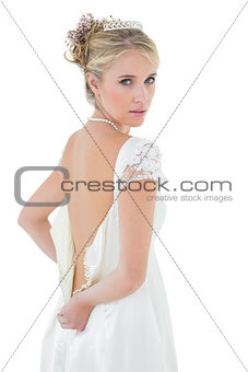 Beautiful bride getting dressed over white background