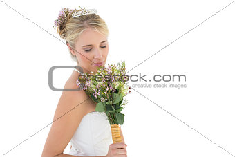 Bride smelling flower bouquet over white background