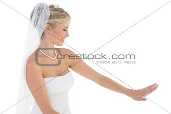 Beautiful bride looking at wedding ring over white background