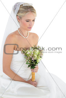 Thoughtful bride holding flower bouquet