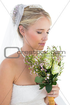 Bride smelling bouquet over white background