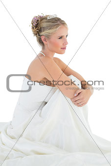 Bride hugging knees over white background