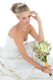 Bride looking at rose bouquet against white background