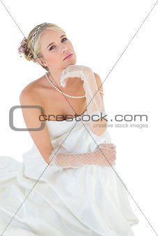 Sensuous bride with hand on chin against white background