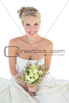 Bride holding flower bouquet against white background