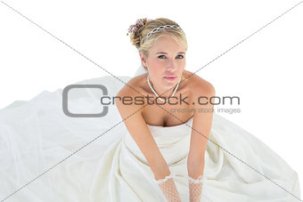 Portrait of elegant bride sitting over white background