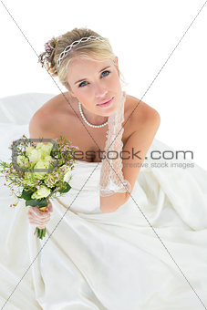 Portrait of sensuous bride holding flower bouquet