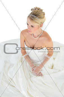 Bride thinking while sitting over white background