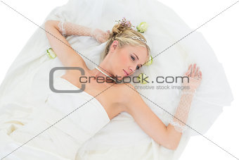 Bride lying while contemplating over white background
